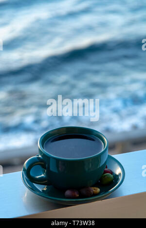 Cup with black coffee served outside with sea view close up - Stock Image