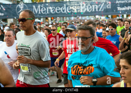 Male runners focused on their race at start of 2014 Mercedes Benz Corporate Run in Miami, Florida, USA. - Stock Image