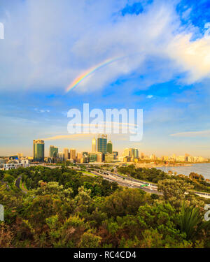 Perth Australia. The city glowing in the late afternoon sun with a rainbow overhead as viewed from the lookout in  Kings Park, Perth,Western Australia - Stock Image