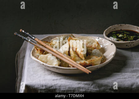 Fried asian dumplings Gyozas potstickers in white ceramic plate served with chopsticks and bowl of soy onion sauce over linen table cloth. Asian dinne - Stock Image