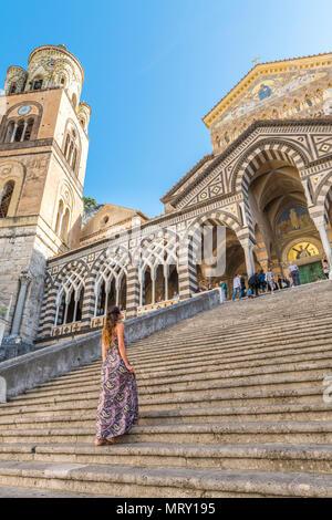 Amalfi, Amalfi coast, Salerno, Campania, Italy. A young woman climbs the staircase of the Amalfi cathedral - Stock Image