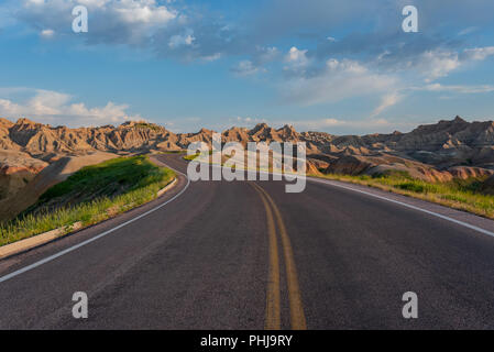 Road Winds Through Badlands Rock Formations on Early Summer Morning - Stock Image