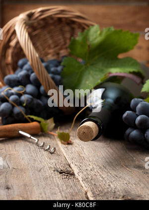 bottle of wine and grapes in basket on old wooden background - Stock Image