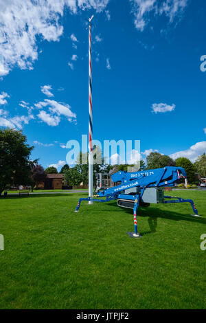 Blue mobile elevating work platform (MEWP) at the foot of a village Maypole for maintenance purposes. - Stock Image
