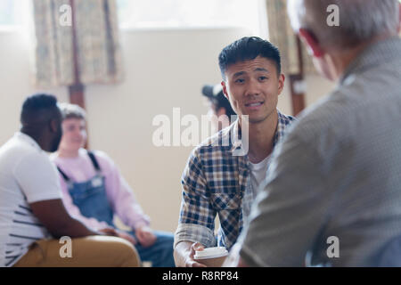 Men talking in group therapy - Stock Image