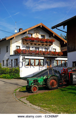 A tractor is parked in the barn of a neighbor of Gasthof Fischerwirt Bernau am Chiemsee, Germany. - Stock Image