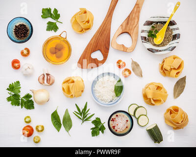 Italian foods concept and menu design. Dried homemade Fettuccine with heart shaped wooden spatula and  ingredients sweet basil ,tomato ,garlic ,parsle - Stock Image