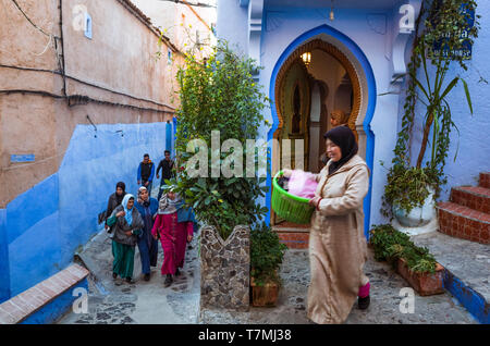 Chefchaouen, Morocco : Moroccan women walk past a blue-washed door in the alleyways of the medina old town. - Stock Image