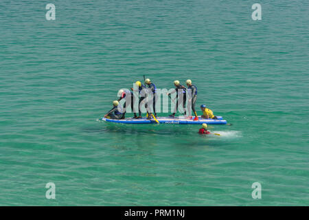 Giant Stand-Up / SUP Paddle Board with group of paddlers. - Stock Image