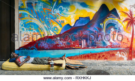 Afro-Brazilian man sleeps rough on a street with a mattress in front of a colourful mural depicting Ipanema Beach, Rio de Janeiro, Brazil - Stock Image