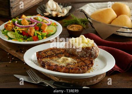Kanas City Bone in Strip Steak with baked potato, salad, and dinner rolls - Stock Image
