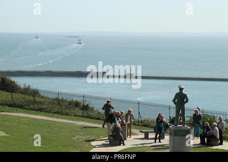 Dover, Kent, UK - September  30 2018:  Tourist stand by a statue of Admiral Sir Bertram Home Ramsay overlooking the Dover port wirh ferries sailing towards Calaris. General view of the coastal town of Dover and the  medieval Dover Castle overlooks the town from the iconic White Cliffs.. Credit: David Mbiyu - Stock Image