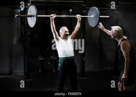 Senior men training with barbell in dark gym - Stock Image