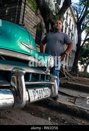 Taxi driver beside his old American car in the centre of Havana, Cuba - Stock Image