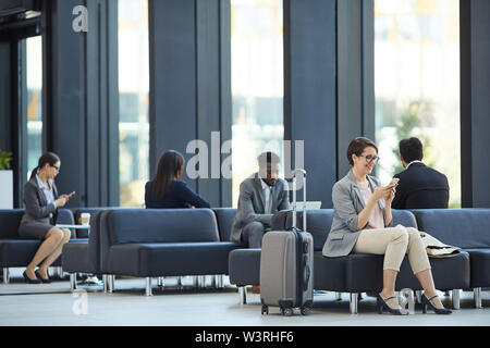 Business people wasting time in airport: cheerful attractive woman sitting on sofa and reading interesting articles on internet - Stock Image