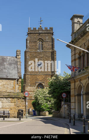 Street scene from the market town of Towcester, Northamptonshire, UK; to the rear the church of St Lawrence and on the right the Town Hall. - Stock Image