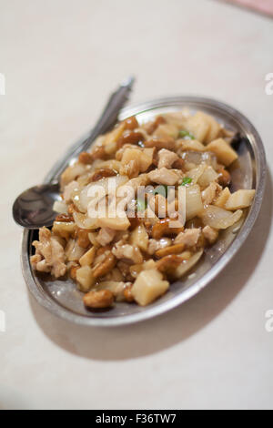 cashew chicken onions Chinese food on metal dish from above - Stock Image