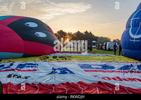 Ballons inflating at sunrise during the Northampton Balloon festival. - Stock Image