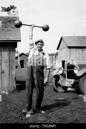 A farmer in Nebraska demonstrates his strength lifting a barbell in the barnyard, ca. 1920. - Stock Image