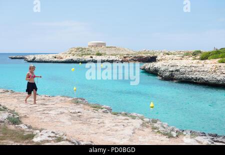 A woman walks along the coast near Torres Des Castellar in Menorca, Spain - Stock Image
