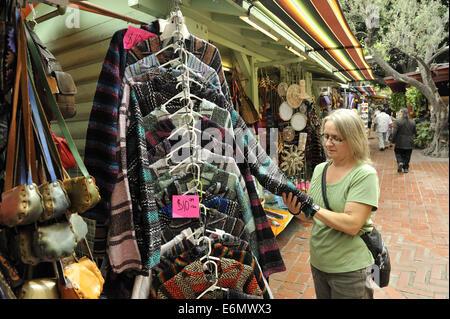 Woman inspecting clothing in market, Calle Olvera, or Olvera Street. El Pueblo de Los Angeles Historic Monument, - Stock Image