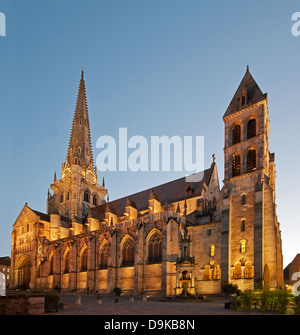 Autun Cathedral north side with evening light and floodlights showing gothic spire and 19th century Romanesque west - Stock Image