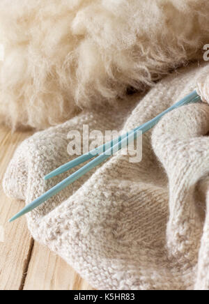 knitted fabric made of natural wool, knitting needles and wool on old wooden background - Stock Image