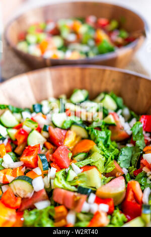 Vertical closeup of two fresh salad in wooden bowls plates with romaine lettuce and bell peppers - Stock Image