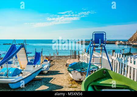 Pedal boats on the sandy beach on the Ligurian coast of Monterosso al Mare on a sunny summer day in Cinque Terre - Stock Image