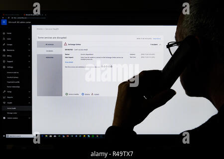 IT support man holding phone to ear whilst looking at computer screen showing faults with Microsoft Office 365 email system - Stock Image