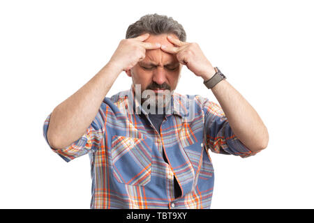 Man touching forehead with fingers as having headache isolated on white studio background - Stock Image