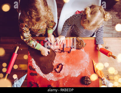 Top view of two young girls sisters rolling cookie dough and making sweet crunchy gingerbread cookies. Fun Christmas winter seasonal family activity. - Stock Image