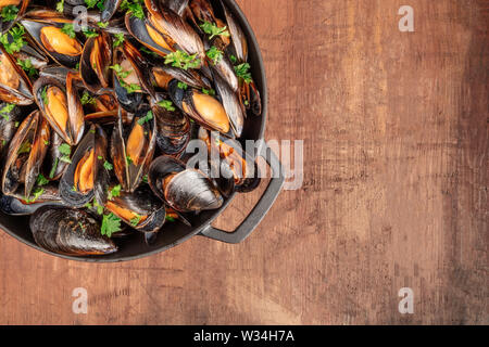 Marinara mussels cooked in a cooking pan, on a dark rustic background with a place for text, overhead close-up shot - Stock Image