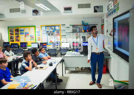 Male teacher leading lesson at touch screen in classroom - Stock Image