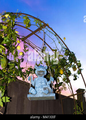 Cute, smiling dragon garden ornament on a swing, in front of an arch with growing Passion flower / Passiflora, against - Stock Image