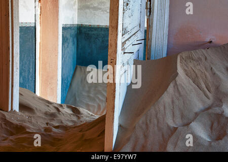 Open doors in a room full of sand in Kolmanskop, a ghost mining town in Namibia, Africa. The desert has reclaimed - Stock Image