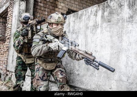 Pair of soldiers in action in a ruined city. - Stock Image