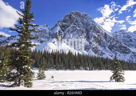Winter Landscape View of Frozen Snow Covered Taylor Lake and Rugged Peaks in Banff National Park Canadian Rocky Mountains - Stock Image