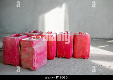 Red used canisters on the construction site indoors on the grey wall background - Stock Image