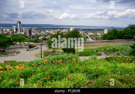 Overlook Hamilton city landmarks and waterfront skyline with landscaped flowerbeds on top of Niagara Escarpment along Blue Trail in cloudy day in summ - Stock Image