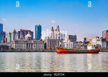1 December 2018: Shanghai, China - Cargo ship on the Huangpu River passing The Bund, the historic business area of Shanghai. - Stock Image