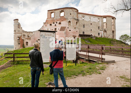 Janowiec Castle exterior and people reading about history on the visitor information board in front of the bridge - Stock Image