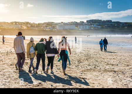 A group of friends walking down to the sea at Fistral Beach in Newquay in Cornwall. - Stock Image