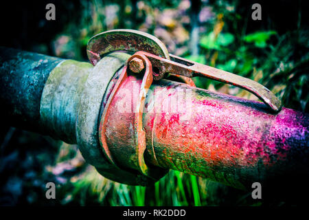 Old colorful metal pipes with clutch on dark background with blurred grass. Coupling of red and blue pipeline close-up. Cohesiveness, fixed connection. - Stock Image