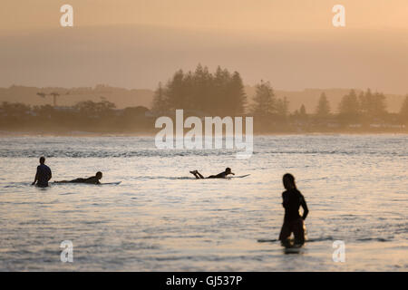People surfing at Byron Beach in Byron Bay. - Stock Image