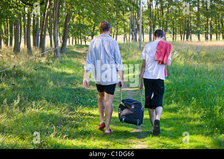 Man and boy carrying a heavy bag together. - Stock Image