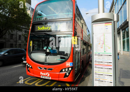 A red double-decker London bus passes a bus stop showing a stylised map and timetables. Bus frequencies; public - Stock Image