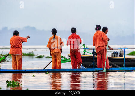 Women getting ready to practice boat racing on Inle Lake in preparation for the Phaung Daw Oo Festival in October. Shan State Myanmar - Stock Image