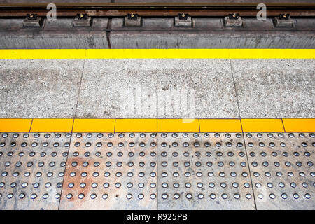 tactile paving at platform edge also called detectable warning surface to assist visually impaired pedestrians, no people - Stock Image