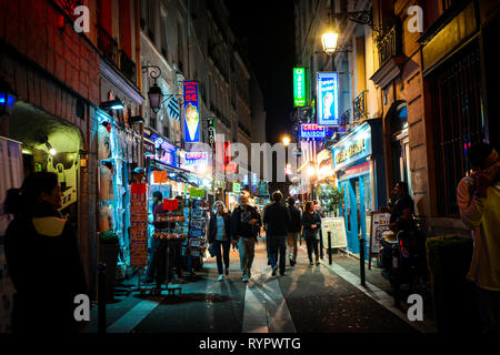 Tourists pass shops and cafes as they walk the colorful neon streets late at night in the Latin Quarter section of Paris France - Stock Image